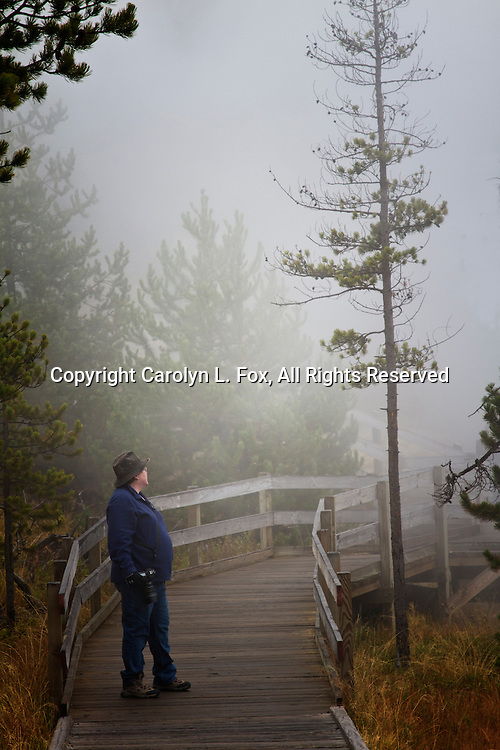 A woman stands on a small bridge gazing out at the foggy Yellowstone landscape. She's holding a camera in one hand.