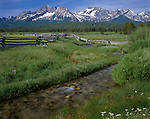 Sawtooth National Recreation Area, ID<br /> Small stream and wood rail fence cuts through a grassy meadow with peaks of the Sawtooth Range in the distance