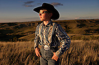 Decked out in a black hat, shades and big belt buckle, young rancher Drew Kuntz checks cattle while helping out his aunt and uncle on their ranch in North Dakota.