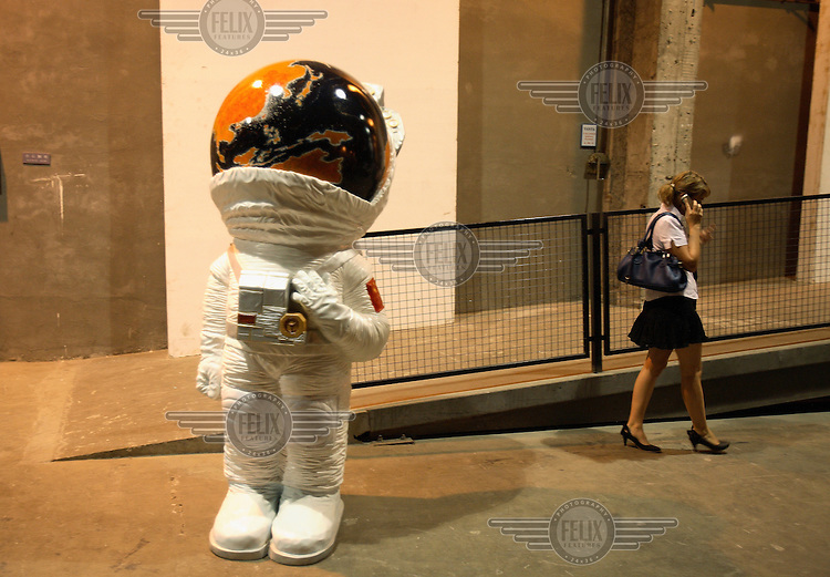 A woman walks by a model of a taikonaut during the Pecha Kucha Night at the Shanghai Sculpture Space in Shanghai. Pecha Kucha is a presentation format in which (mostly creative) work can be easily and informally shown.