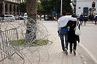 Tunisia, il dopo Rivoluzione: una<br /> coppia di giovani abbracciati passeggia nel centro di Tunisi accanto ad una transenna con il filo spinato.<br /> TUNISIA after spring revolution, couple of teenagers