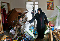 "Palestinian woman inspect her home follwing Israeli shelling in Gaza City. Israel threatened to target leaders of the Islamist Hamas movement in the Gaza Strip after a child hit by shrapnel in a rocket attack on southern Israel had a leg amputated.""photo by Fady Adwan"""