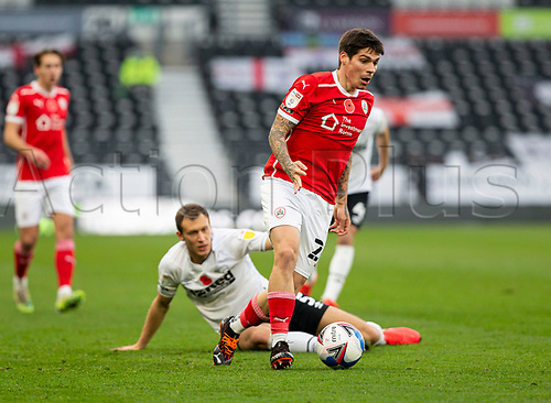 7th November 2020; Pride Park, Derby, East Midlands; English Football League Championship Football, Derby County versus Barnsley; Dominik Frieser of Barnsley with the ball as he gets away from Matthew Clarke of Derby County seated on the grass