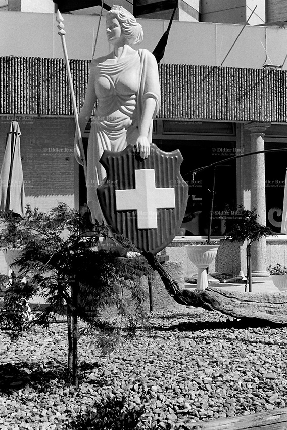 Switzerland. Canton Ticino. Bellinzona. Hotel Garni Liberty. A statue of Helvetia on the hotel's terrace. Helvetia is the female national personification of Switzerland, officially the Swiss Confederation.The allegory is typically pictured in a flowing gown, with a spear and a shield emblazoned with the Swiss flag, and commonly with braided hair, commonly with a wreath as a symbol of confederation. The flag of Switzerland consists of a red flag with a white cross (a bold, equilateral cross) in the centre. It is one of only two square sovereign-state flags. 16.05.2017 © 2017 Didier Ruef