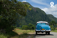 Vintage car on country road, rear view, Vinales, Cuba (Licence this image exclusively with Getty: http://www.gettyimages.com/detail/sb10061763b-001 )