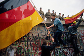 West Berlin, West Germany<br /> November 11, 1989<br /> <br /> Two German men hold German flags at the Berlin Wall. The East German government lifts travel and emigration restrictions to the West on November 9, 1989.