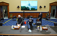 Dr. Anthony Fauci, Director, National Institute for Allergy and Infectious Diseases, National Institutes of Health, reads papers as a worker cleans a table prior to a House Committee on Energy and Commerce hearing on the Trump Administration's Response to the COVID-19 Pandemic, on Capitol Hill in Washington, DC on Tuesday, June 23, 2020. <br /> Credit: Kevin Dietsch / Pool via CNP/AdMedia