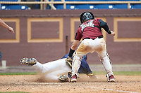 Cameran Brantley (32) of the North Carolina A&T Aggies slides across home plate ahead of the tag by North Carolina Central Eagles catcher Chet Sikes (7) at Durham Athletic Park on April 10, 2021 in Durham, North Carolina. (Brian Westerholt/Four Seam Images)