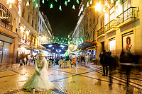 Lisbon, Portugal - December 23: People are seen walking by a human statue in downtown Lisbon, Portugal December 23, 2019. <br /> The Christmas lights in Lisbon are getting more sophisticated and stunning each time, they are an attraction to locals and tourists to choose Lisbon as a place to spend the holidays<br /> (Photo by Luis Boza/VIEWpress/Corbis via Getty Images)