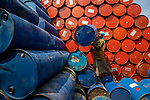 """Pictured:   Workers at a depot in Bangladesh sort through thousands of brightly painted oil barrels.<br /> <br /> The colourful containers, used for storing fuels including petrol, diesel and octane are unloaded from lorries at the site in Narayanganj, before being stored and returned to oil companies to be reused.<br /> <br /> The images were captured by Azim Khan Ronnie.  Azim said, """"More than one thousand barrels are sorted through every day, with each one capable of holding 250 litres of oil.  The site holds around 20,000 barrels.""""<br /> <br /> """"The empty barrels are taken off the lorries and separated depending on whether they are metal or plastic.  Workers here earn £5 a day.""""<br /> <br /> Please byline: Azim Khan Ronnie/Solent News<br /> <br /> © Azim Khan Ronnie/Solent News & Photo Agency<br /> UK +44 (0) 2380 458800"""