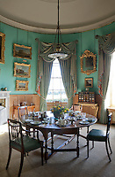 A private dining room, its turquoise, curved walls hung with paintings collected on the Grand Tour