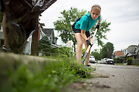 """Sally Finkel uses a shovel to dig up weeds along a curb in the Hawthorne neighborhood during """"Circle the City with Service,"""" the Kiwanis Circle K International's 2015 Large Scale Service Project, on Wednesday, June 24, 2015, in Indianapolis. (Photo by James Brosher)"""