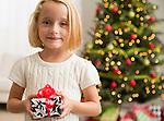 Girl (6-7) holding Christmas present