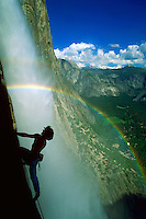 A rainbow appears to surround a climber beside Yosemite Falls in Yosemite National Park, California with snow covered mountains, clouds and blue sky in the background.<br />