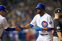 Chicago Cubs Dexter Fowler (24) shakes hands with first base coach Brandon Hyde after hitting a single in the eighth inning during Game 3 of the Major League Baseball World Series against the Cleveland Indians on October 28, 2016 at Wrigley Field in Chicago, Illinois.  (Mike Janes/Four Seam Images)