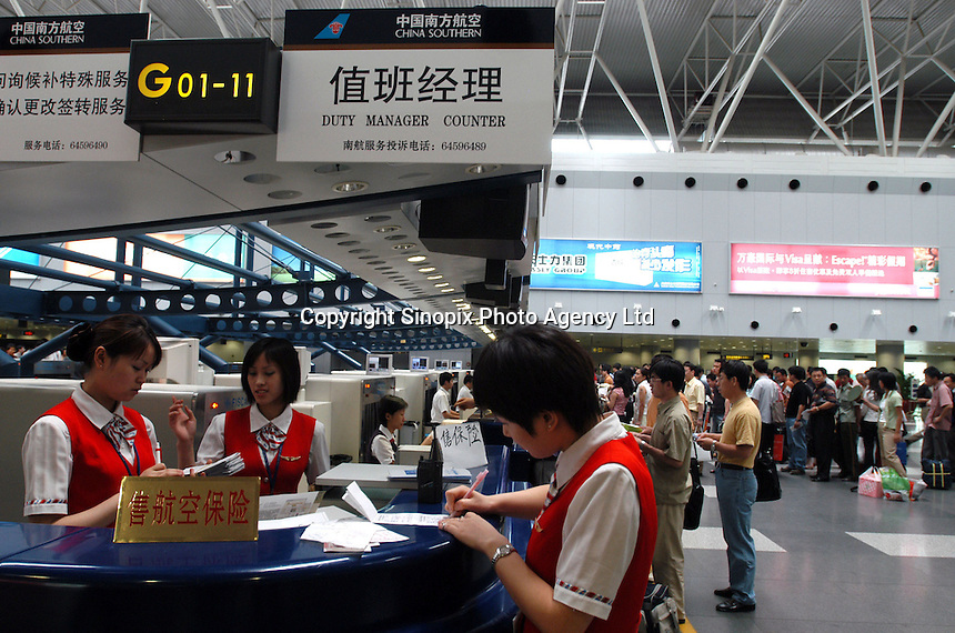 China Southern Airlines check-in counter staff work at Beijing International Airport. China 's biggest carrier by fleet size said it plans to raise 2.7 billion yuan (US$326 million) selling shares to domestic investors for the first time, raising money to buy Boeing Co. aircraft..07-JUL-03