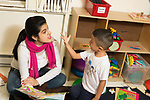 Education Preschool 2-3 year olds therapist or intern working with boy in classroom