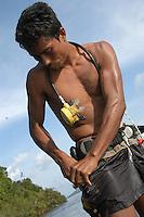 Damilton Rodrigues da Costa 29 anos casado duas filhas, trabalha com pesca de peixes ornamentais desde os 16 anos  e seu aprendiz Edson da Costa Gomes de 15 anos se preparam com equipamentos prec·rios para mergulhar nas ·guas do rio Xing˙ para capturar centenas de peixes ornamentais e vendÍ-los para empresas exportadoras que trabalham com os mercados da ¡sia, China e Europa e chegam a mandar para fora do paÌs mais de 200.000 mil espÈcimes por mÍs.Altamira, Par·, Brasil.10/02/2006Foto Paulo Santos/Interfoto