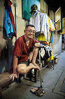 Thailand. Bangkok. An old man, sitting on a wood bench and wearing a pair of shorts, lives in Tha Tian. His clothes are hanged outside of his small house which is located in the oldest buildings of Tha Tian. Tha Tian is a community located in the downtown area and in the center of the urban historic district, called Koh Rattanakosin. 28.03.09 © 2009 Didier Ruef