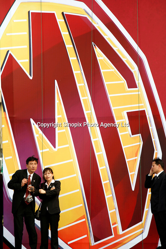 Nanjing Automobile Corporation (NAC) employees stand in front of a large MG billboard outside of the launching ceremony of the first Chinese built MG vehicles in Nanjing, China. The Chinese company is now in a position to take on Rover's assets and plan its future. It intended to relocate the engine plant and some car production plant to China but to retain some car production plant in the UK..27 Mar 2007