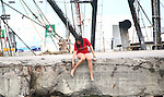 Young attractive woman sits on the ledge of a commercial fishing  dock.