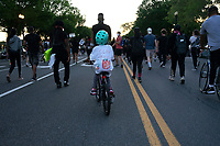 A child rides their bike through the crowd during a protest in Washington, D.C., U.S., on Sunday, May 31, 2020, following the death of an unarmed black man at the hands of Minnesota police on May 25, 2020.  Credit: Stefani Reynolds / CNP/AdMedia