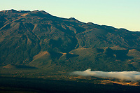 Mauna Kea volcano and the old and future saddle road at sunset viewed from the 11,000 foot elevation of Mauna Loa volcano the Big Island of Hawaii