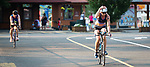 MIDDLEBURY, CT 070721JS18 Cassandra Maximenko of Watertown, right, adjusts her helmet as she takes to the bike portion during the 35th annual Pat Griskuus Triathlon held Wednesday at Quassy Amusement Park in Middlebury. Maximenko would go on to win the female division. <br /> Jim Shannon Republican American