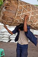 Myanmar, Burma, Yangon.  Manual Laborer Carrying Load to Boat in the Yangon River.