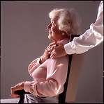 Seated older woman toching hand of younger woman