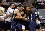 SIOUX FALLS, SD - MARCH 8: Kevin Obanor #0 of the Oral Roberts Golden Eagles is mobbed by teammates after he tipped in the winning shot at the buzzer to defeat the South Dakota State Jackrabbits 90-88 during the Summit League Basketball Tournament at the Sanford Pentagon in Sioux Falls, SD. (Photo by Richard Carlson/Inertia)
