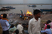 Mourners sit on the ghats while the dead body of their relative burn in the background at the Harishchandra Ghat in the ancient city of Varanasi in Uttar Pradesh, India. Photograph: Sanjit Das/Panos