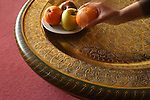 A hand pick up fruits from a traditional style handmade copper plate. Fes. Morocco