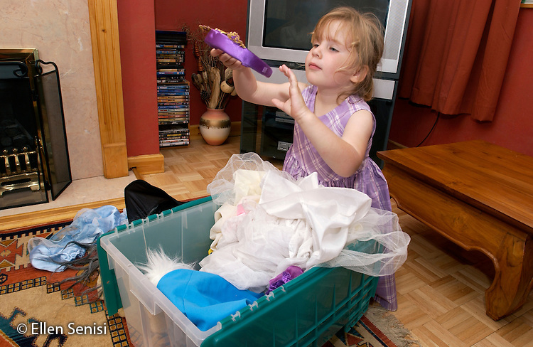 MR / Radley, Abingdon, Oxfordshire, England.Girl (5) looks through box of dress-up clothes in her living room..MR: Web4.©Ellen B. Senisi