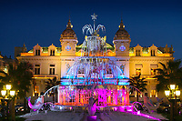 The Monte Carlo Casino resort, with the fountain decorated and lit up at dusk for Christmas, in Monaco French Riviera (Côte d'Azur) France Europe