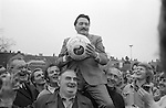 Royal Shrovetide Football. Ashbourne, Derbyshire, England 1974. Annually Shrove Tuesday and Ash Wednesday.<br /> <br /> Mr Don Lowndes, Ashbourne resident and Turner-upper on Ash Wednesday 1974 is carried shoulder high through town by John Mansfield and Colin LeGrice, before the start of the Royal Shrovetide football game. At Shaw Croft the crowd sing Auld Lang Syne and God Save the Queen before Lowndes kisses the ball, and throws it up, to start the match.