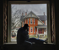 Construction supervisor sits in the window of Flowers by Doris where construction began restoring the old home.