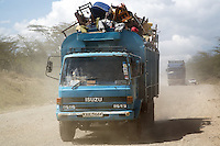 Kenya. Rift Valley province. 20 km outside Nakuru. 23.01.2008. A truck heavily loaded drives on a the dirt road and carries various items and black Kikuyu men, all IDPS fleing from the inter-ethnic strifes. The men save some belongings, such as chairs, tables, mattresses, bikes,... Internally displaced persons (IDPs) are people forced to flee their homes but who, unlike refugees, remain within their country's borders. The Kikuyu are Kenya's most populous ethnic group. © 2008 Didier Ruef