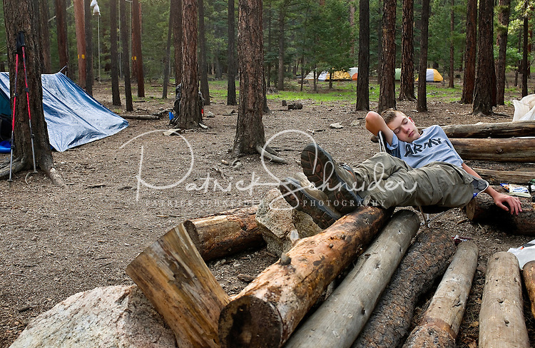 Photo story of Philmont Scout Ranch in Cimarron, New Mexico, taken during a Boy Scout Troop backpack trip in the summer of 2013. Photo is part of a comprehensive picture package which shows in-depth photography of a BSA Ventures crew on a trek.  In this photo a  BSA Venture Crew members takes a break on a makeshift log seating area, after climbing the natural rock surfaces at  Cimarroncito Camp in the backcountry at Philmont Scout Ranch.   <br /> <br /> <br /> The  Photo by travel photograph: PatrickschneiderPhoto.com