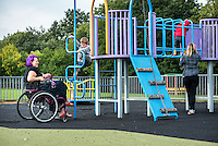 """A mother who is sitting in her wheelchair breastfeeds her baby, just a few weeks old, whist watching other children in a playground.<br /> <br /> Image from the breastfeeding collection of the """"We Do It In Public"""" documentary photography picture library project: <br />  www.breastfeedinginpublic.co.uk<br /> <br /> <br /> Berkshire, England, UK<br /> 27/09/2013<br /> <br /> © Paul Carter / wdiip.co.uk"""