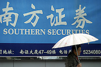 A woman holding an umbrella walks past a billboard for Southern Securities in Shanghai, China. The Shenzhen based securities firm, the nation's fifth largest with over Euro 330 million (420 million US) in stock shares, has been taken over by government regulators under suspicions of illegal practices. The Chinese government had for years been trying to rein in its unruly stock markets and boost investor confidence in the transparency of their business practice..05-JAN-04
