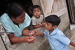 A Mayan mother talks to two young boys through a window of her house in the Mayan community of San Miguel, Toledo, Belize