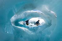 Hikers with blue ice cave on Franz Josef Glacier, Westland Tai Poutini National Park, West Coast, UNESCO World Heritage Area, New Zealand, NZ