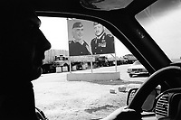 """Jordan. At the jordano -iraqi border. Profile of a taxi driver and portraits of King Abdullah II and his father King Hussein, both are wearing military clothes as high ranking Commander in chief of the Army. His Majesty King Abdullah II bin Al Hussein, is the actual King of The Hashemite Kingdom of Jordan.His Majesty King Abdullah II bin Al Hussein is the 43rd generation direct descendant of the Prophet Muhammad. He assumed his constitutional powers as Monarch of the Hashemite Kingdom of Jordan on February 7th, 1999, the day of the death of his father, the late Royal Highness King Hussein bin Talal (1935-1999), known to his  people as Al-Malik Al-Insan (""""The Humane King"""").  © 2004 Didier Ruef"""