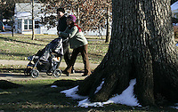 parent walking baby in stroller in park