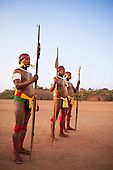 Xingu Indigenous Park, Mato Grosso, Brazil. Aldeia Matipu. Sagagi Matipu, Aira Matipu and Lamati Matipu, three elders, stand sentine during the kuarup funeral ceremony. They have spent the whole night guarding the village against the possibility of evil spirits gaining access during the kuarup.