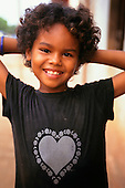 Amazon, Brazil. Smiling little girl of mixed blood with a heart on her t-shirt, holding her hands on her head.
