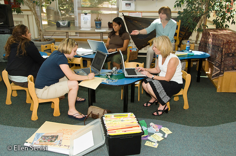 MR / College Park, Maryland.Center for Young Children, laboratory school within the College of Education at the University of Maryland. Full day developmental program of early childhood education for children of faculty, staff, and students at the university..A group of teachers and teaching assistants use both paper work and computers to prepare lesson plans during their planning time in a large multi-use common space at the school. At front right is a large filing box to file student portfolios..MR: AH-gPcyc.© Ellen B. Senisi
