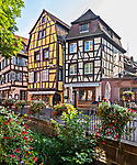 Shops and restaurants in half-timbered buildings line the canal in Colmar, Alsace