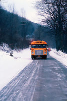 School bus stopped to drop off along a snow cover road.